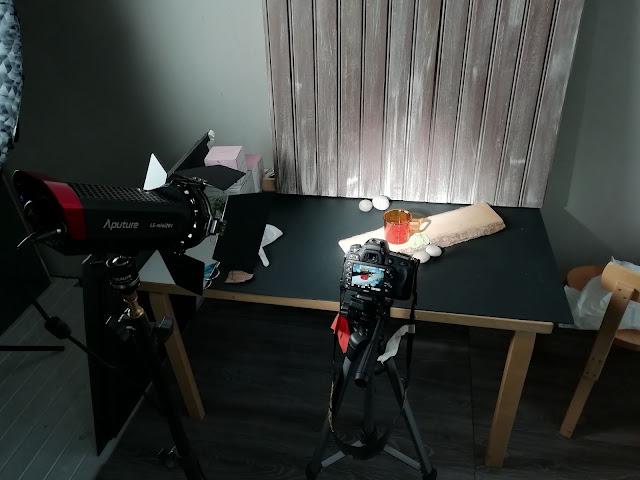 Kuvaustilanteessa otettu kuva Muurlan meripihka lasimukista ja samalla näyetty kuvauslokaatiota