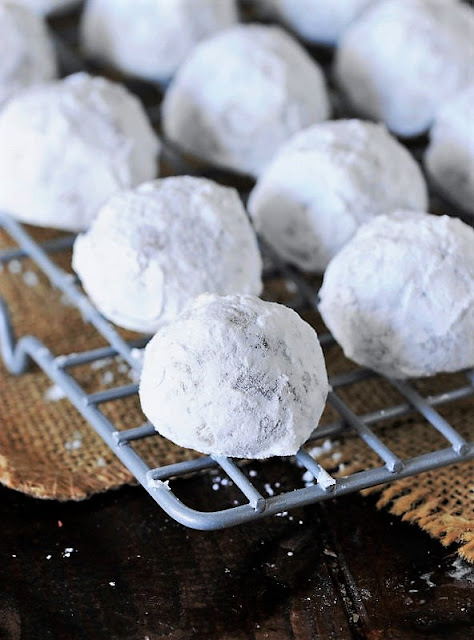 Red Velvet Snowball Cookies on Cooling Rack After Second Roll in Confectioners Sugar Image
