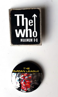 "The Who badge is a black rectangle (portrait orientation), almost square, with white writing: ""The Who"" in lower case letters, with ""The"" above ""Who"". The right hand leg of the lower case 'h' in 'The' becomes the tall stem of the lower case 'h' in 'who'. A vertical arrow pointing up is leading from the 'o' of 'who'.  Underneath the band name, in capital letters ""MAXIMUM R&B"".  Below ""The Who"" badge is a badge for ""The Human League"".  Printed on silver hologrammatic metal, there is a black strip across the top with yellow capital letters ""THE HUMAN LEAGUE"" (""THE"" is on the top line and ""HUMAN LEAGUE"" the next). Below the strip is a line drawing of hands ripping open a shirt to reveal a red heart which is in the shape of a face."