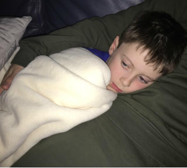 boy snuggling under a duvet