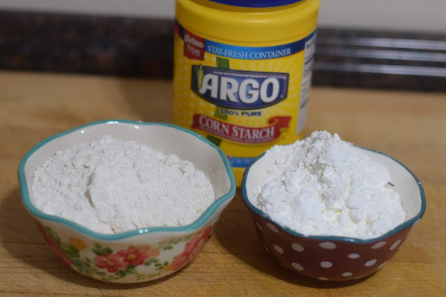 A small bowl of flour and a small bowl of cornstarch on the counter.