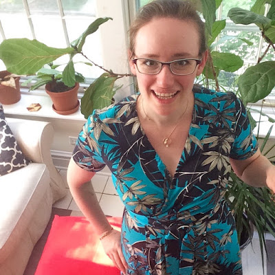 Selfie of me in my turquoise palm print Vogue 8379, showing the slight wrinkling along the neckline resulting from overly tight elastic insertion. Also, there's a lovely houseplant jungle behind me.