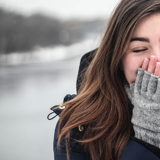 Woman wearing gloves and covering her mouth