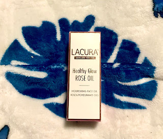 A rectangular white box with lacuna healthy glow rose oil in rose gold font on a bright background