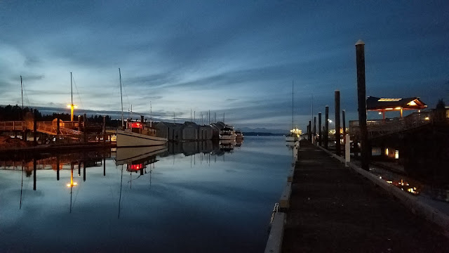 Docks glow under lamp-light at a marina in Olympia Washington. The Olympic Mountains are barely visible under in the disappearing sunlight.