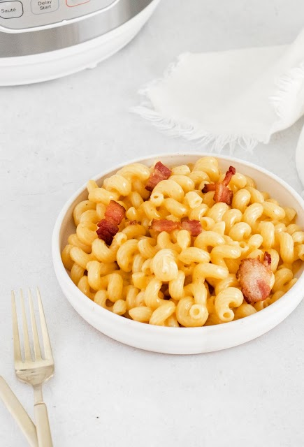 Instant Pot Bacon Macaroni and Cheese in a bowl with white Instant Pot in the background