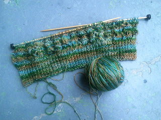 Flat Knitted lace on two wooden needles, with a bottom edge of ribbing. The yarn is a fingering weight, and varigated blue-green-brown.
