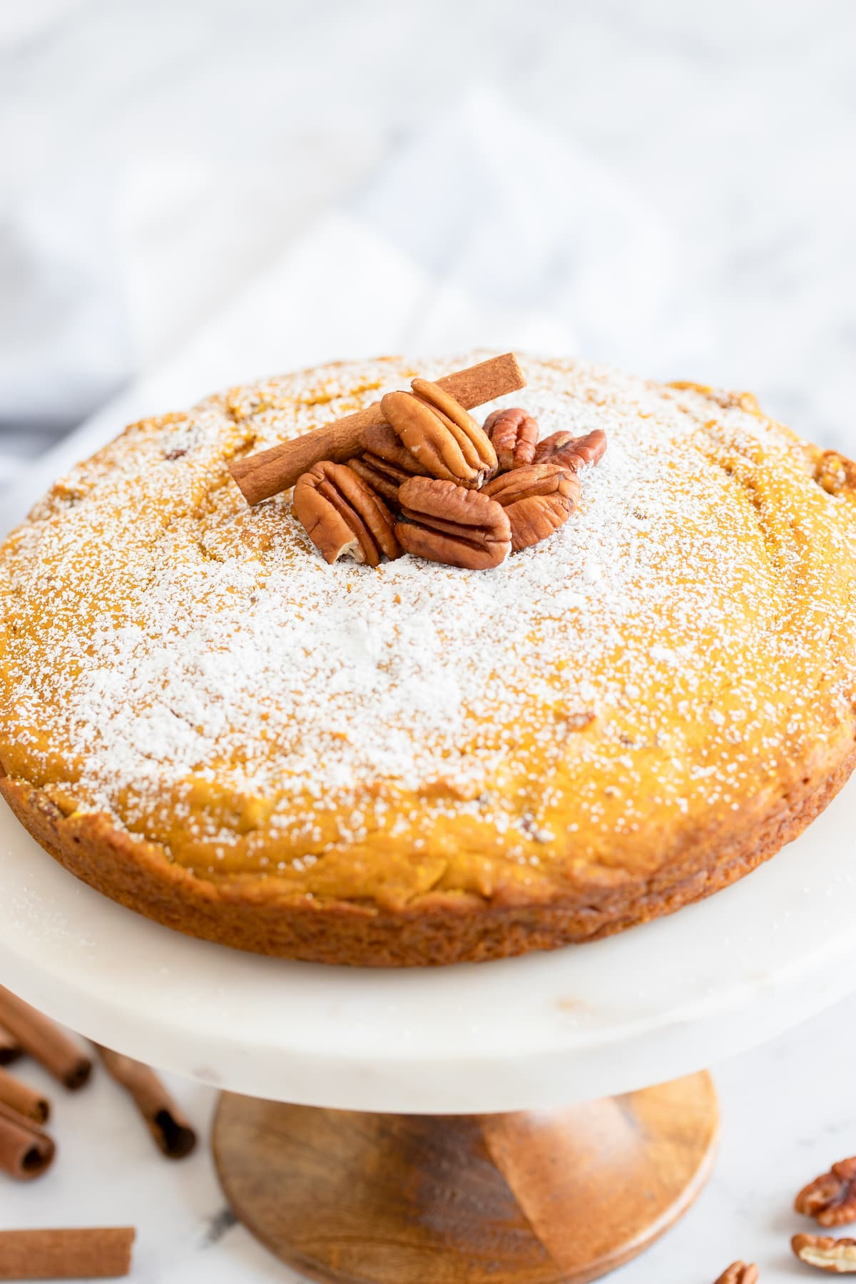 Pumpkin Crunch Snacking Cake dusted with powdered sugar and a pile of pecans in the center on a cake stand.