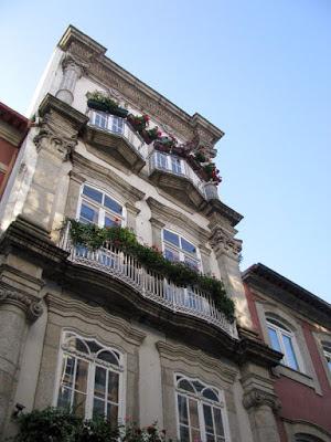 fachada de casa com varandas e vasos de flor