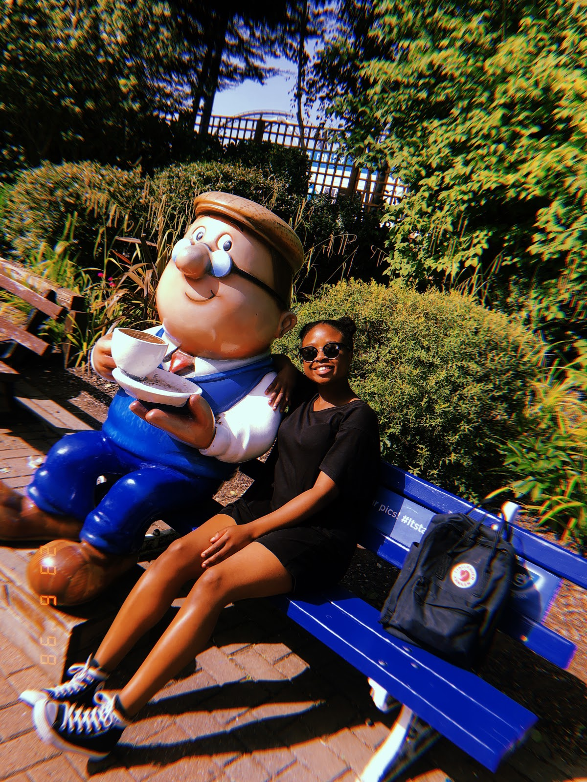A Polaroid style shot of me sitting on a bench next to a cartoon character