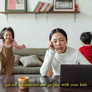 mother on her computer while kids are playing