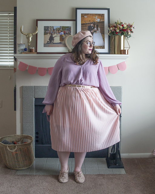 An outfit consisting of pastel pink beret, pastel lavender wrap blouse tucked into a pastel pink pleated midi skirt and pastel pink skirt.