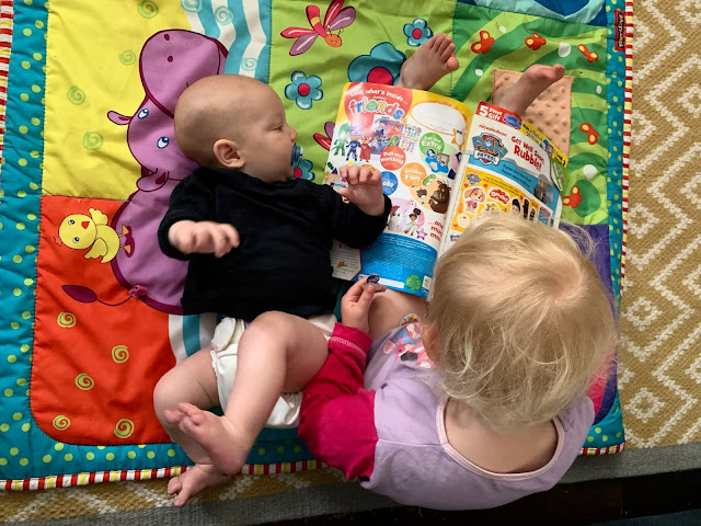 Siblings sitting on a playmat while the toddler reads a magazine and Baby Boy looks at it