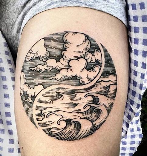 Apesar de não ser uma lua, essa tatuagem tem um conceito intrigante. Um yin-yang tem o tradicional preto e branco design substituído com os elementos do vento e da água.
