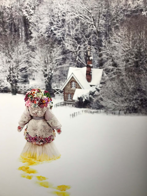 A blonde woman dressed in a romantic flowery dress and overcoat, her bright yellow footsteps show in the deep white snow. She walks towards a brown stone cottage in the forest.