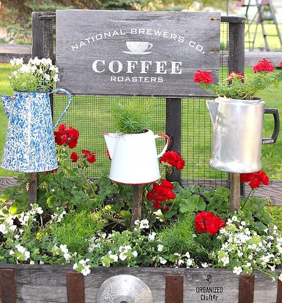 Photo of coffee sign and coffeepot planters on stakes