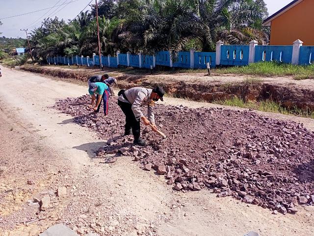 Bhabinkamtibmas Gotong Royong Bersama Warga Perbaiki Jalan Desa