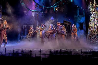Torikohtaus, vasemmassa reunassa Scrooge ja keskellä ihmisjoukko