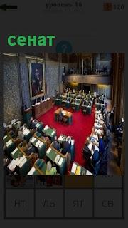 В помещении заседает сенат. В центре стол с председателем и вокруг сидят сенаторы