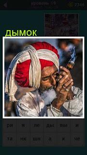 мужчина с тюрбаном на голове прикуривает трубку из которой идет дымок