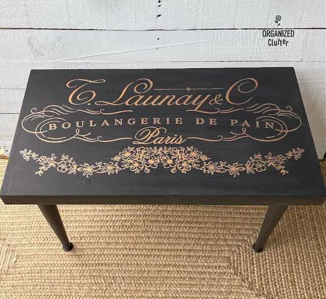 Photo of a thrifted midcentury coffee table painted black with a gold French design transfer.