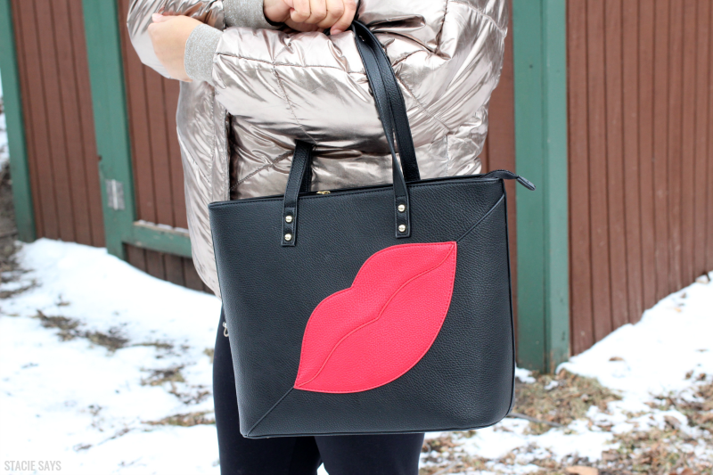 a women wearing a black tote with red lips on it.