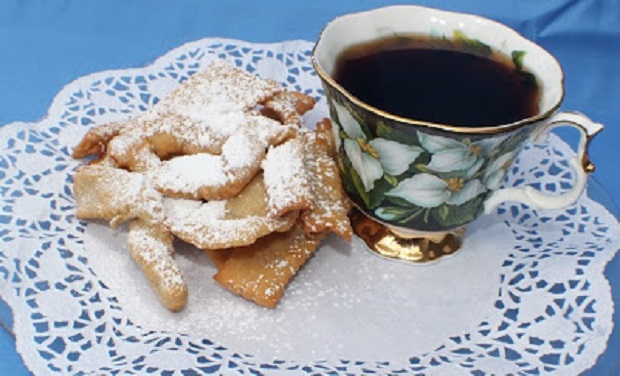 This is a fried thin cookie with powdered sugar on top and a black coffee called espresso in the cup on a white Dollie