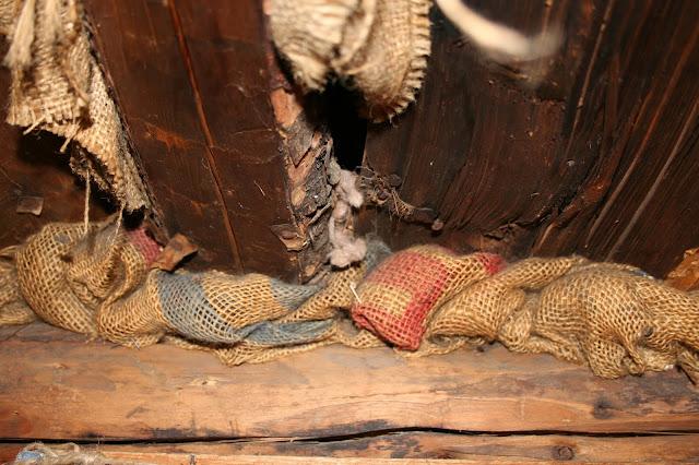 Old burlap sacks fill cracks in an Alaskan log cabin