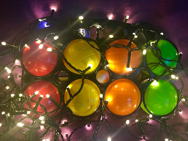 A set of Boules is red, yellow, orange and green surrounded by fairy lights