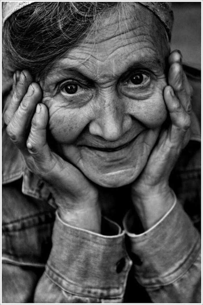 Gorgeous black and white photo of a smiling senior woman, her hands on her cheeks. Best April Fool. MarchMatron.com