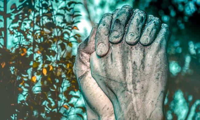A imagem mostra duas mãos completamente sujas de barro cruzadas em gesto de oração.