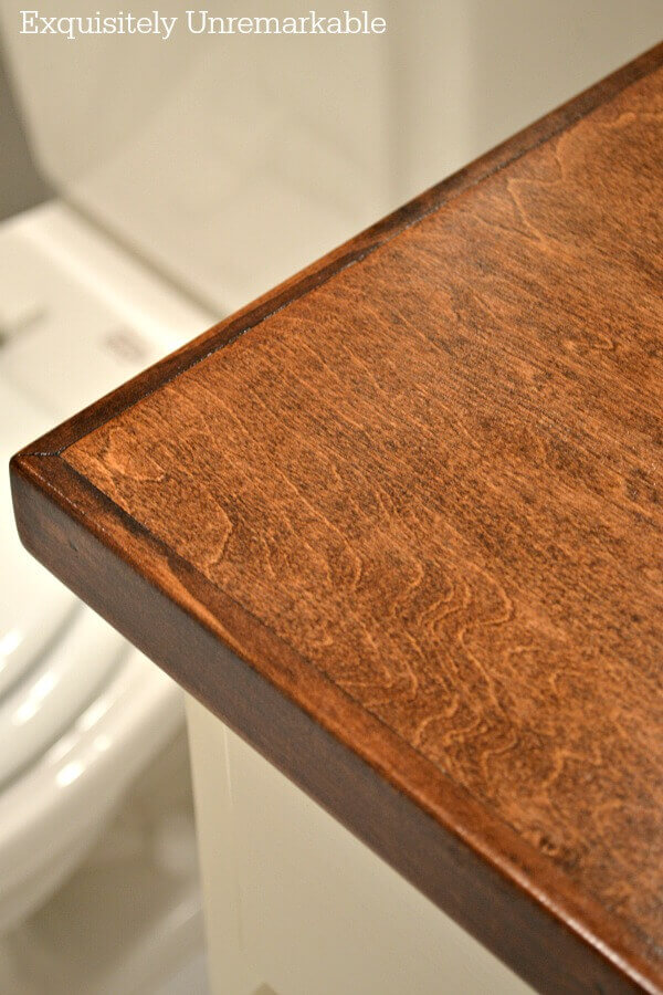 The corner of a stained wooden countertop in a bathroom