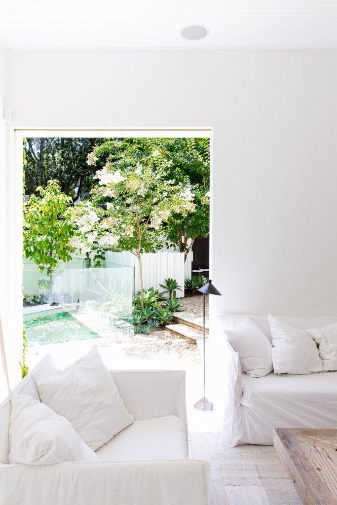 Salón blanco con vista al jardín