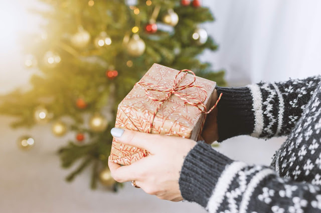 Photo by JESHOOTS.COM on Unsplash offering a gift at Christmas