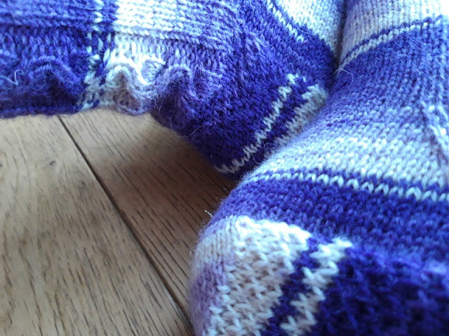 A photo showing a partial view of a pair of socks - the leg of the left leg showing a cable pattern and the heel of the right foot showing Eye of Partridge stitch is visible.  The socks are knitted in Winwick Mum Hidden Gem yarn which is shades of purple and ecru