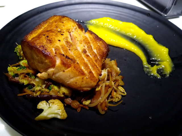 A grilled salmon over some vegetables inside a black plate.