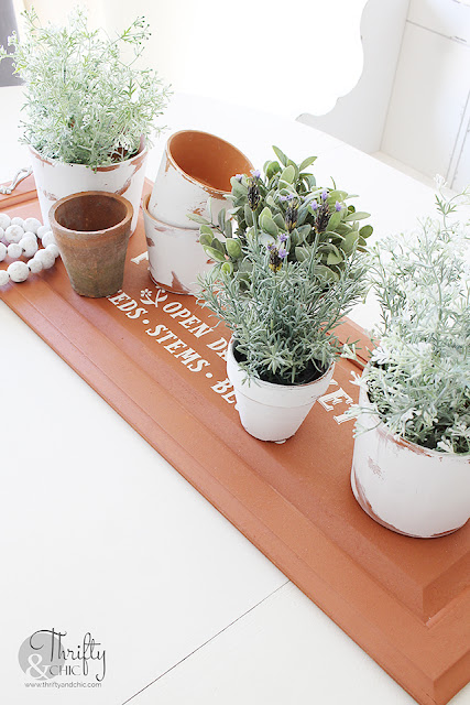 DIY spring dining table decor. DIY spring centerpiece. DIY spring tablescape. DIY faux terracotta tray. DecoArt Suede acrylic paint. DIY repurposed tray. How to make a tray out of a cabinet door. Flower Market design. Spring dining room decor.