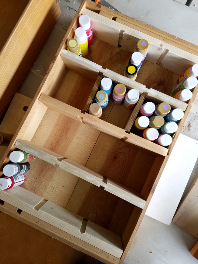 bottles of craft paint getting organized in a wine crate storage bo