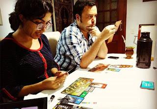 Foto de Nívia e Rennan jogando 7 wonder (ela usando blusa azul marinho, ele ua camisa xadrez)