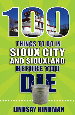 the cover of 100 Things to Do in Sioux City and Siouxland Before You Die by Lindsay Hindman, a lime green book with white and navy letters, and a picture of a riverboat imposed on the number 100