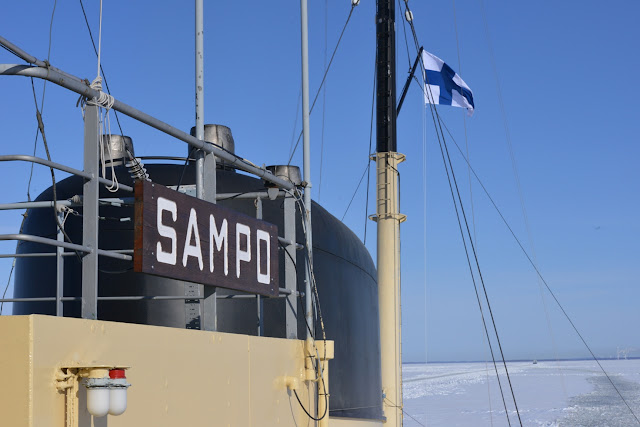 Jäänmurtaja Sampon mastossa liehuu Suomen lippu kun alus kulkee jäissä