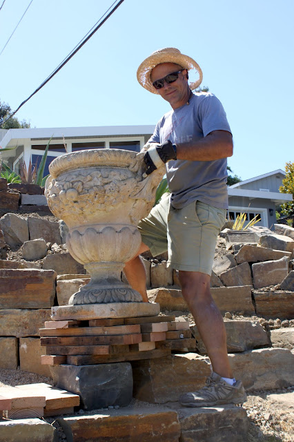 Strong man moving heavy garden urn