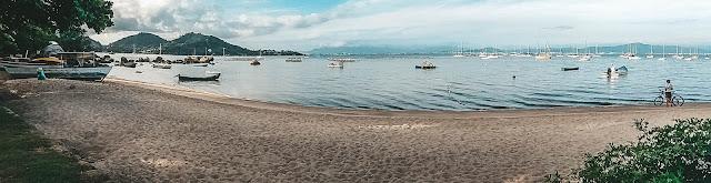 Praia com mar ao fundo e barcos