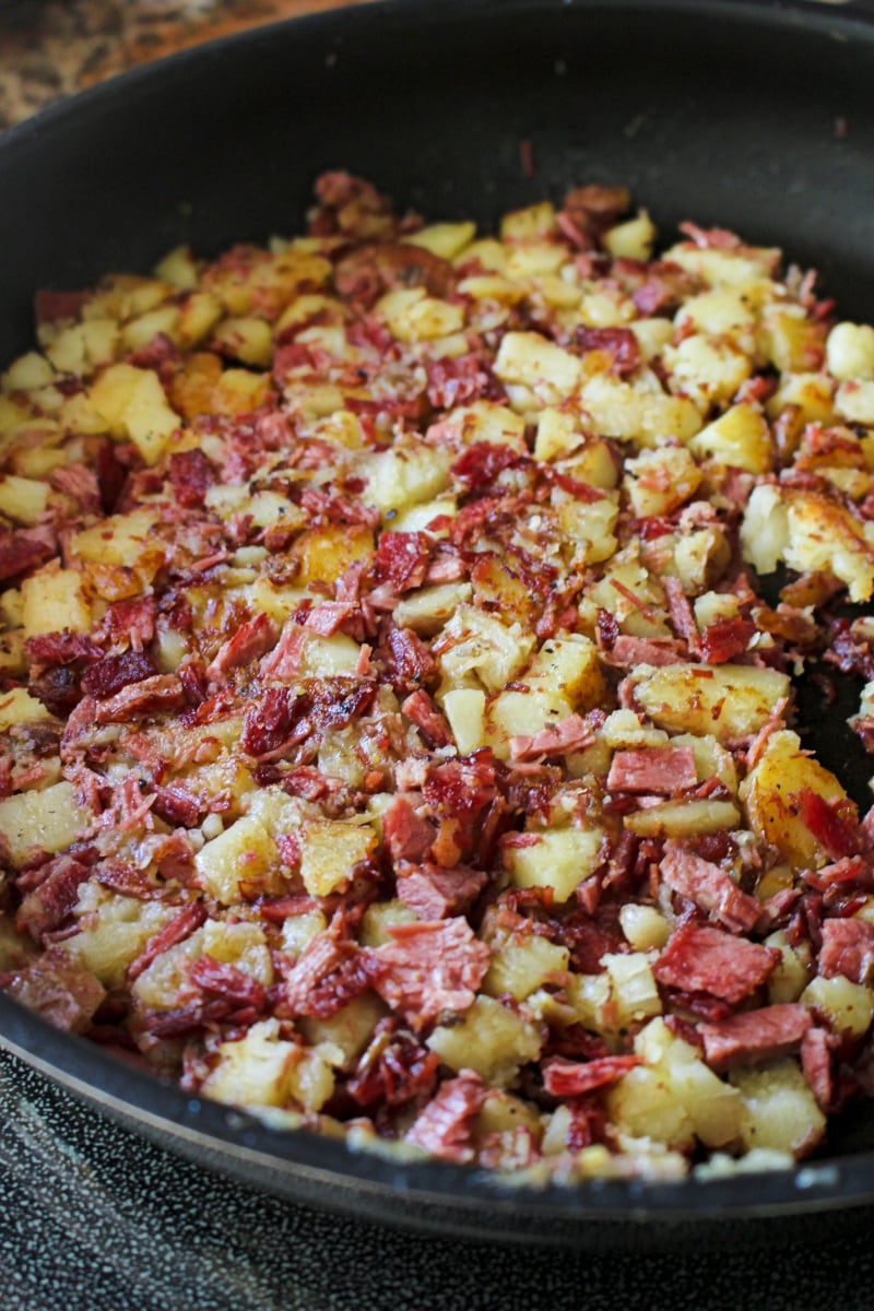 Side view of corned beef and potatoes in a frying pan.