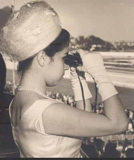 mulher no Jockey Club de chapé e binoculos