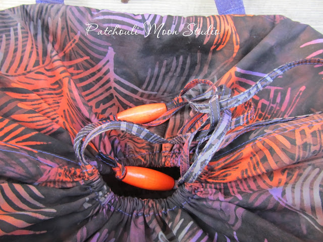 View looking down on the top of the bag with the drawstring top closed. There are large orange beads used at the end of the drawstrings