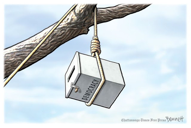 Rope slung over tree limb ending in hangman's noose wrapped around a ballot box labeled