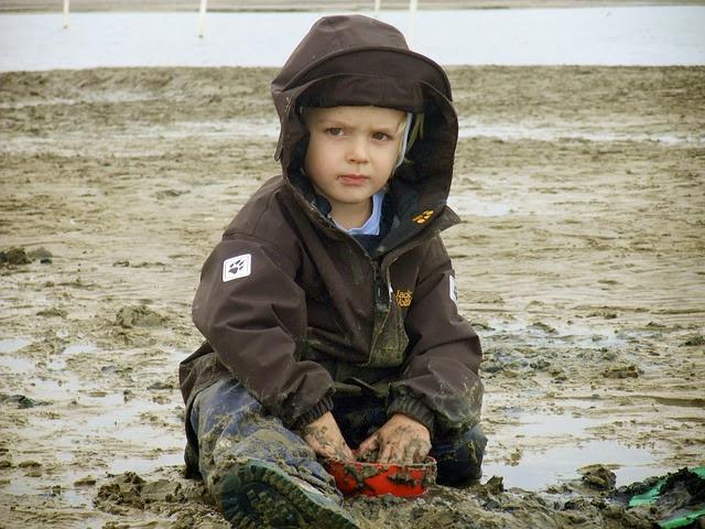 Kind spielt im Matsch