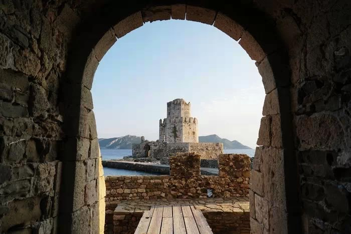 Каменная арка обрамляющая замок и горы