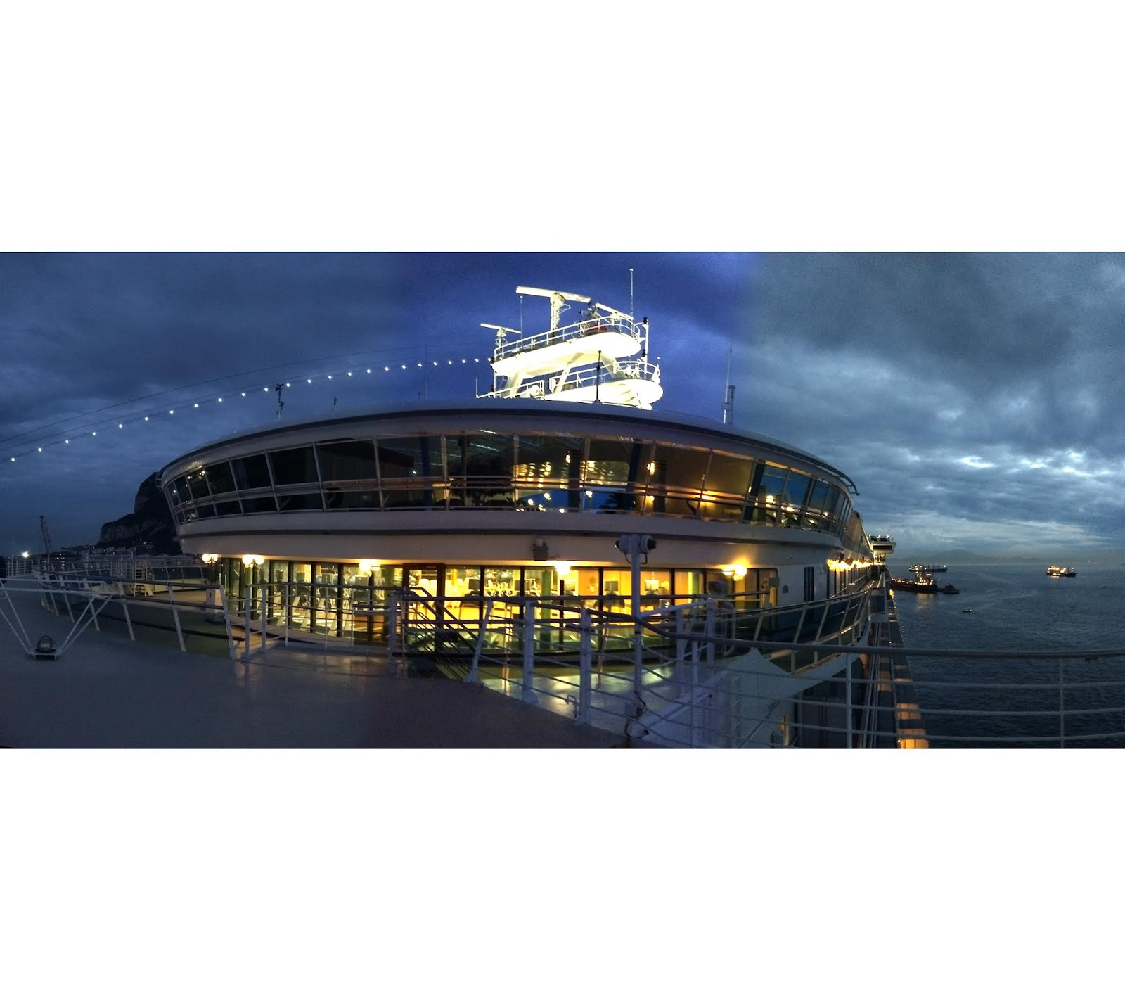 Panoramic view of a lit up gym on a cruise ship at dusk.